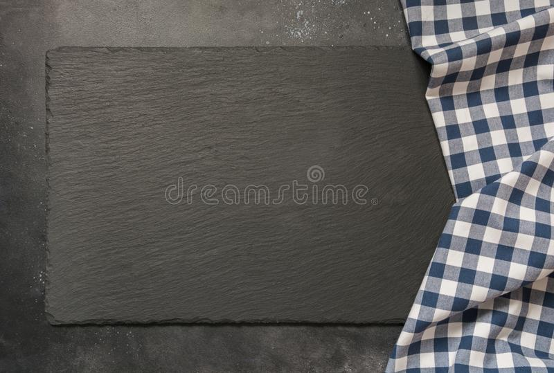 Black slate background with kitchen blue checkered towel. Cooking food, picnic or food background with copy space. Top view. Black slate background with kitchen royalty free stock photos