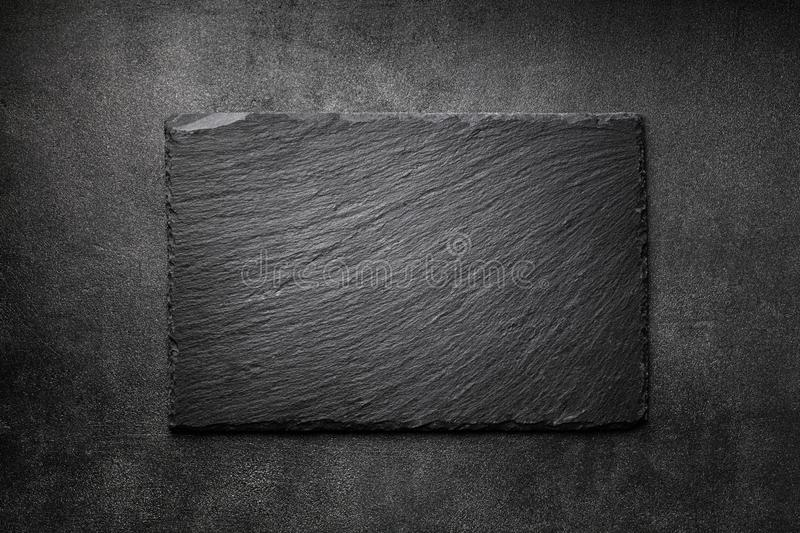 Black slate board on dark stone texture top view. Empty space for menu or recipe stock photography