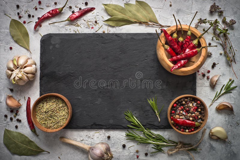 Black slate board, herbs and spices. royalty free stock images