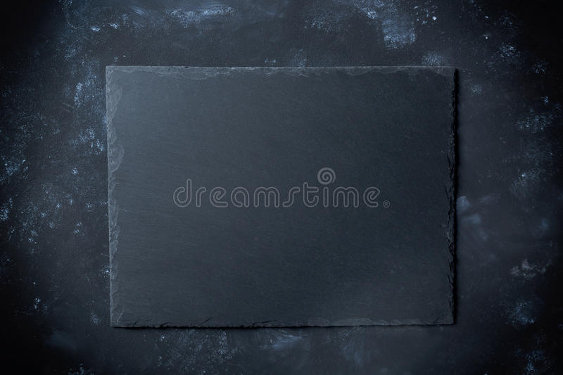 Black slate plate on stone background with top view stock photography