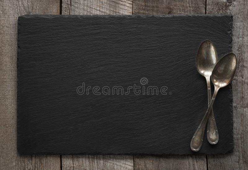 Black slate plate and vintage spoons on wooden board. Space for your text. Black slate plate and vintage spoons on wooden board. Top view. Space for your text stock photography