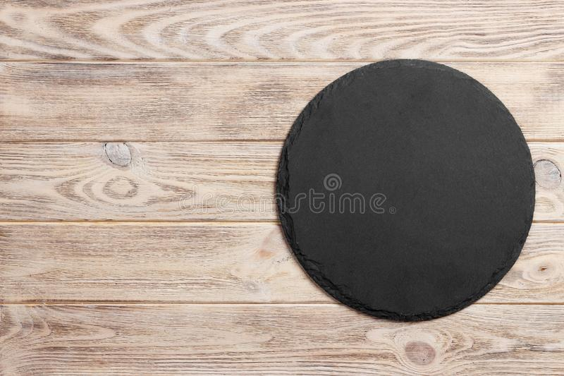 Black slate round stone on wooden background, top view, copy space royalty free stock photo
