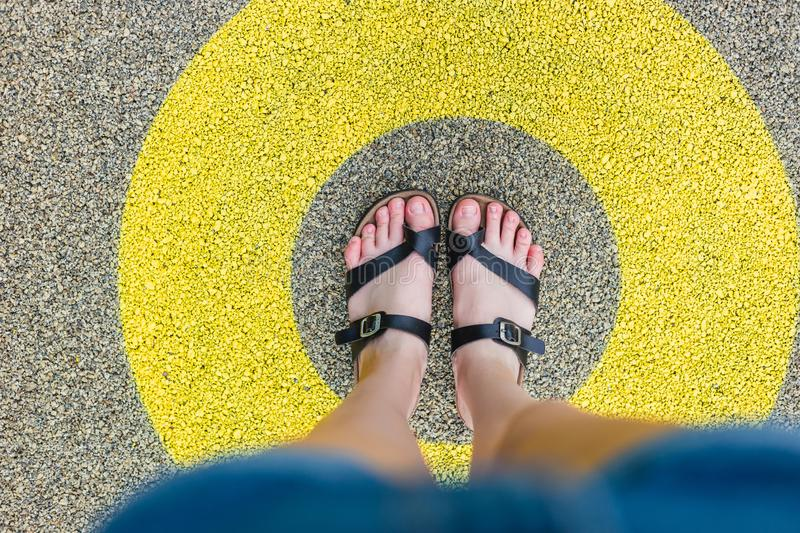 Black slippers standing in yellow circle on the asphalt concrete floor. Concept of limit, boundary, frame, etc. Black shoes standing in white circle on the stock photography