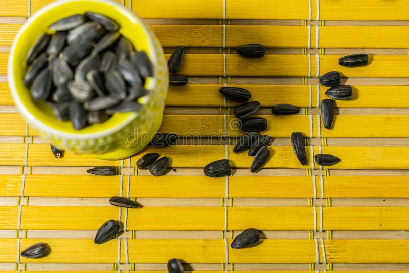 Black small sunflower seeds. Click seeds with husks. A handful in a yellow miniature stand on a wooden napkin. Spilled some seeds. stock photos