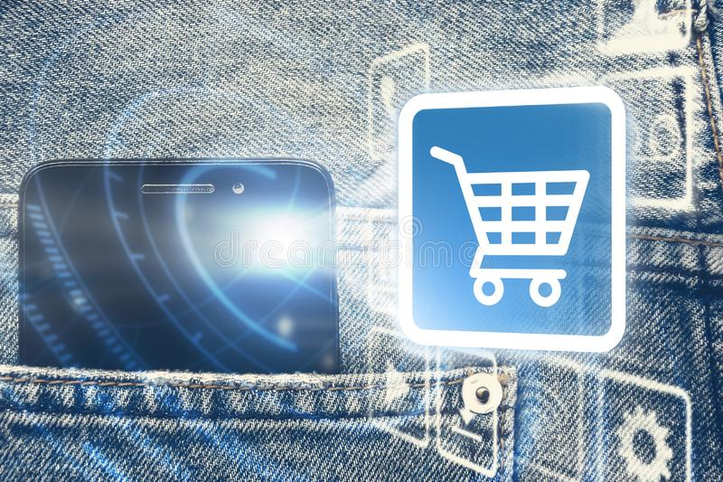 Black smart mobile phone in back blue jeans pocket denim background texture with icon shopping cart and digital graphic.,shopping. stock image