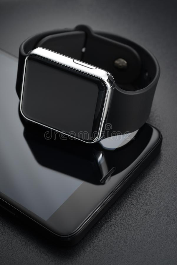 Black smart wrist watches and smartphone royalty free stock photo