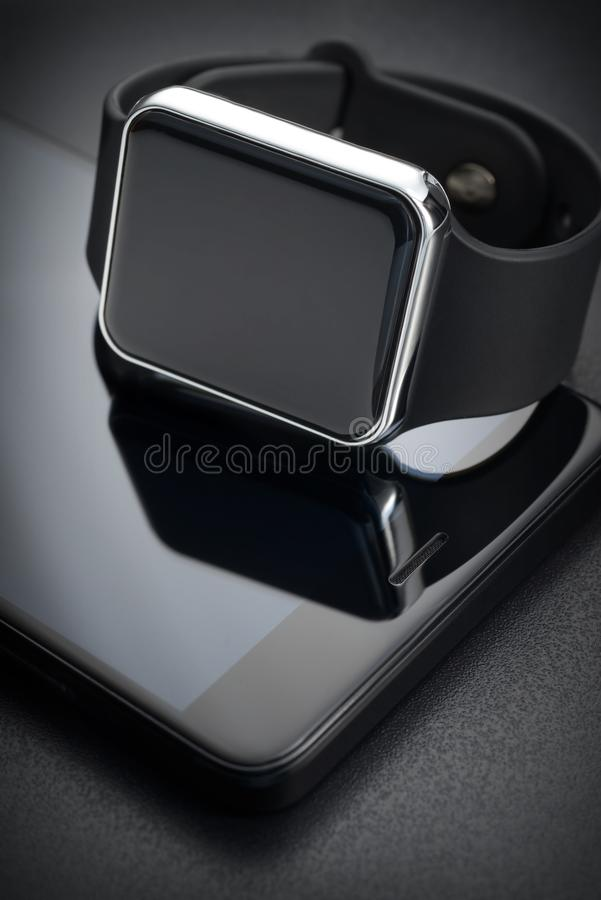 Black smart wrist watches and smartphone stock photography