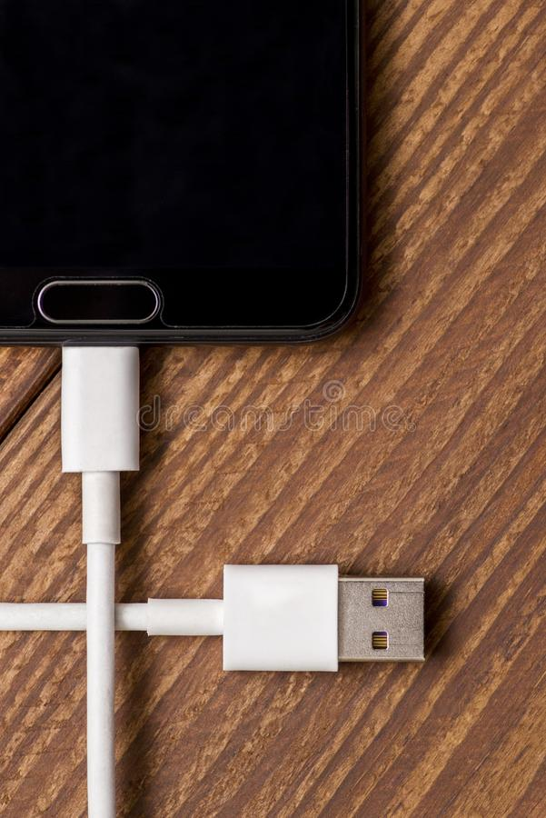 Black smartphone and charging wire with usb connector on wooden background. Mobile phone with white connection plug for charger. stock image
