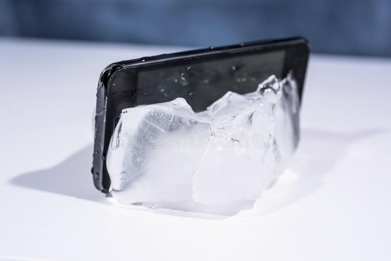 Black smartphone frozen in ice. Abstract object photo.  royalty free stock photography