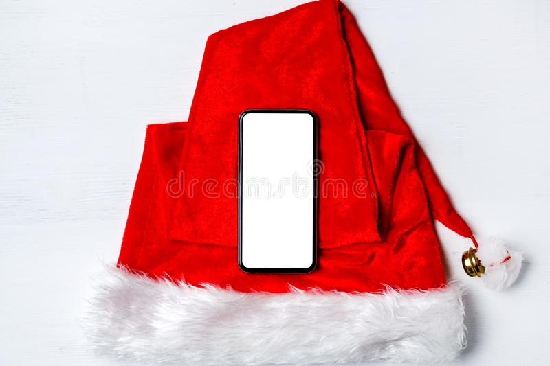 Black smartphone on furry Santa Claus red hat on white wooden background close up stock image