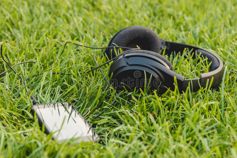 Black Smartphone and Headphones on the Green Grass stock images