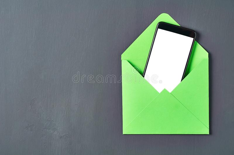 Black smartphone with isolated white screen in green square envelope lies on old scratched dark concrete. Space for text. Top view royalty free stock photo