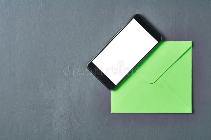 Black smartphone with isolated white screen near green square envelope lies on old scratched dark concrete. Space for text. Top view royalty free stock photography