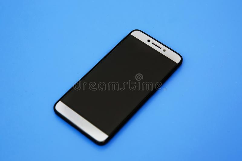 Black mobile smart phone mock up. This smartphone mock-up isolated on blue background. black smartphone with black screen. Android royalty free stock photography