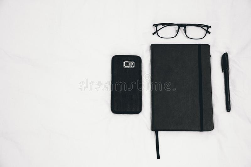 Black Smartphone Beside Planner and Eyeglasses and Pen stock photos