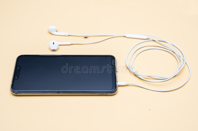 Black smartphone and white earphone stock image