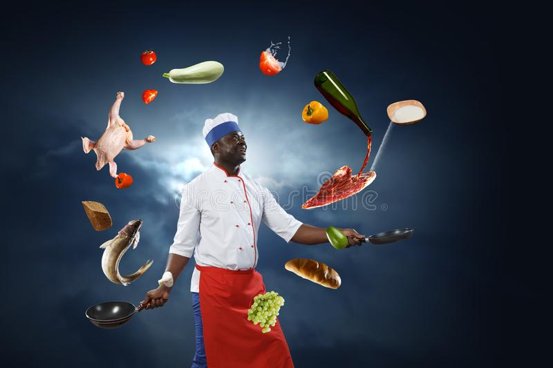 Black chef creative cooking. Mixed media. Black smiling man holding two frying pans with ingredients around him, dark blue sky background royalty free stock photos