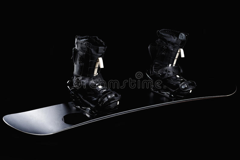 Black snowboard with black bindings and black boots royalty free stock image