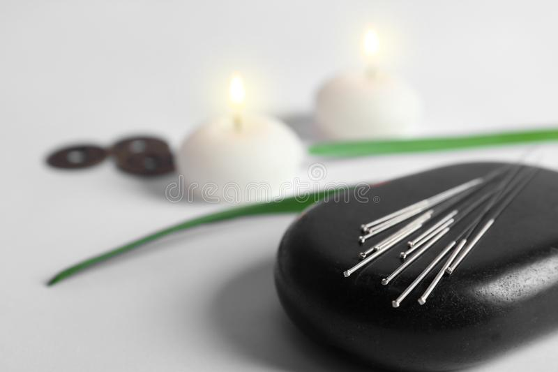 Black spa stone with set of acupuncture needles. On lighted candles blurred background stock photography