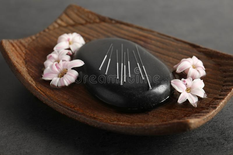 Black spa stone with set of acupuncture needles. On tray stock photography