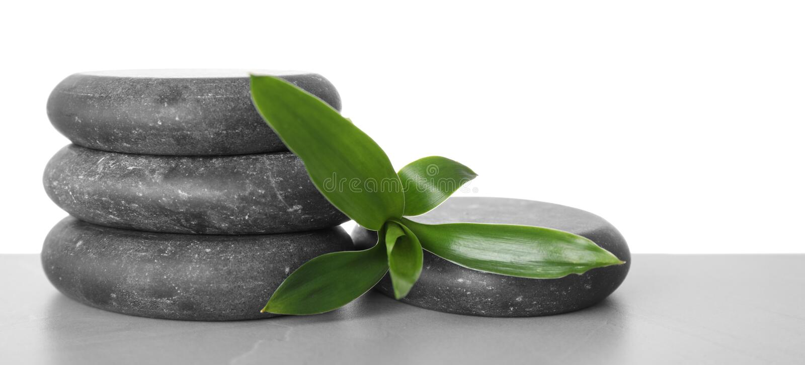 Black spa stones with bamboo on table against white background. Space for text royalty free stock photos