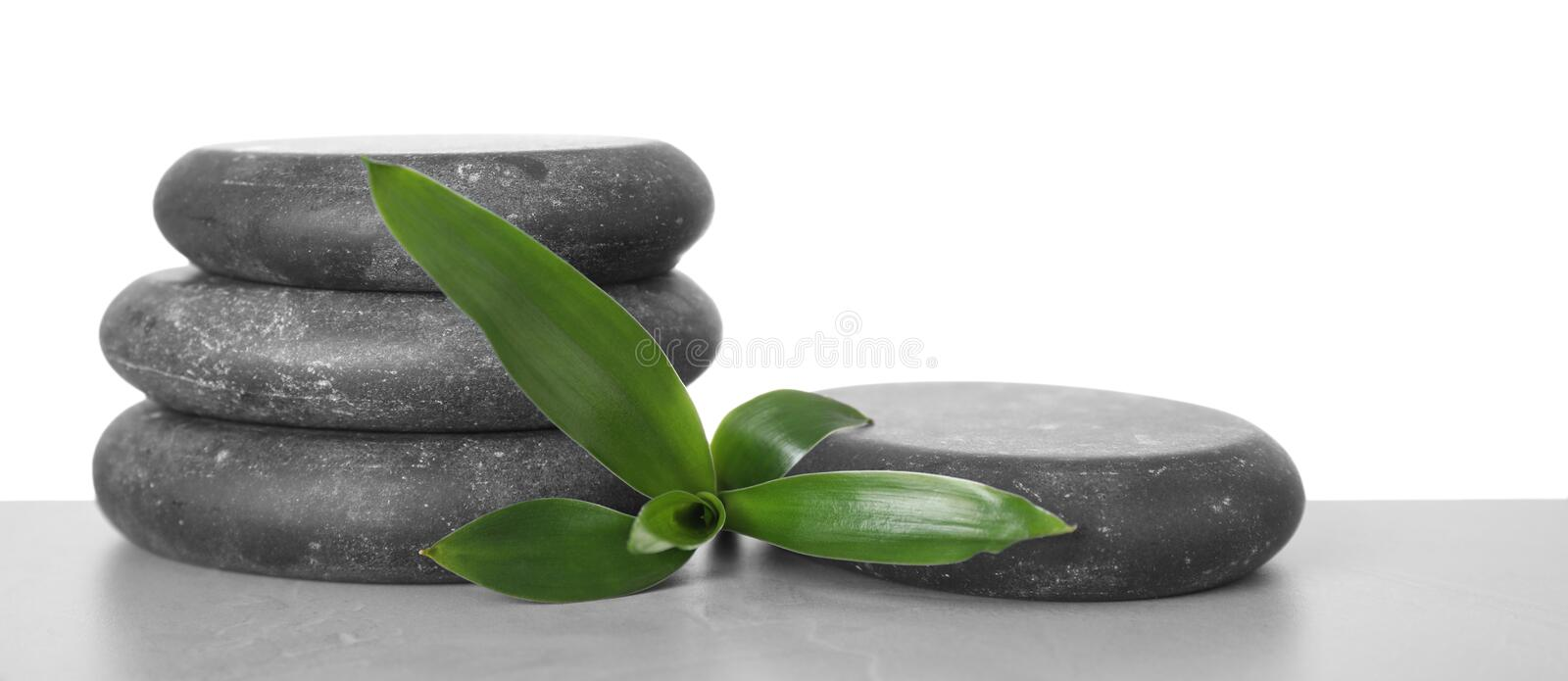 Black spa stones with bamboo on table against white. Background. Space for text stock image