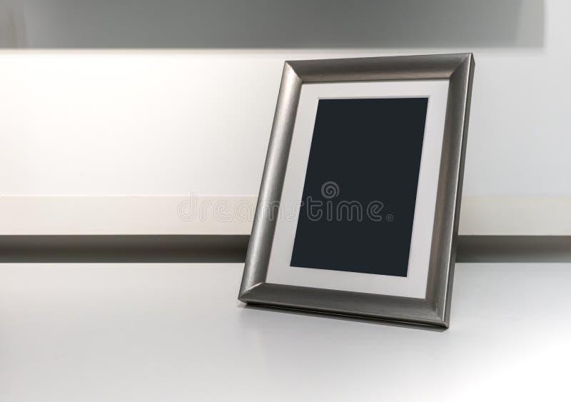 Black space on vertical silver aluminum frame on desk stock image