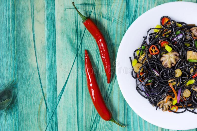 Black spaghetti with seafood and vegetables on a white plate decorated with red pepper green background. Top view royalty free stock image