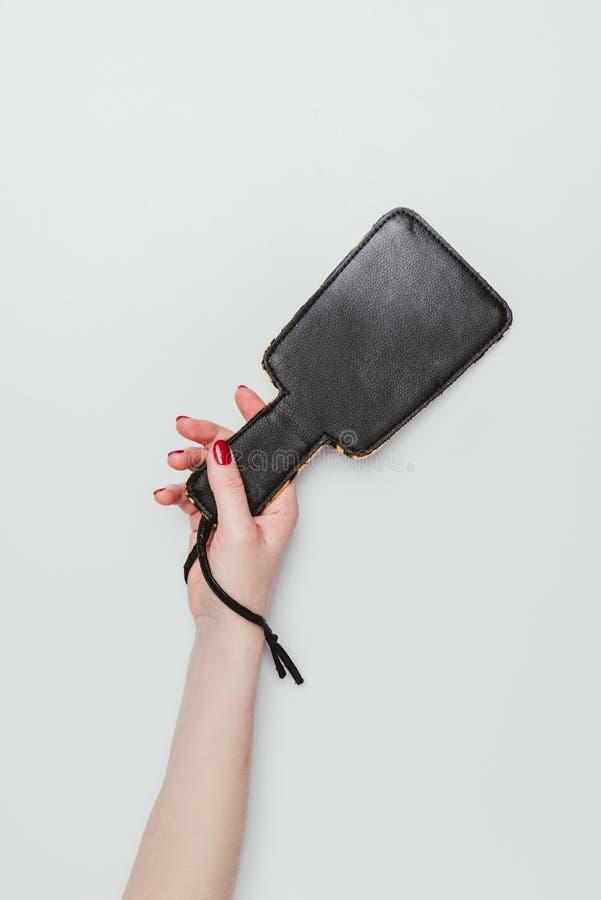 Black spanking paddle in female hand royalty free stock image