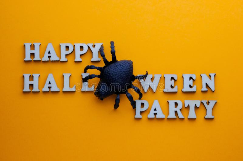 Black spider instead of the letter O on a stylish inscription HAPPY HALLOWEEN PARTY. Words from wooden letters on a bright orange. Background. Template for royalty free stock photos