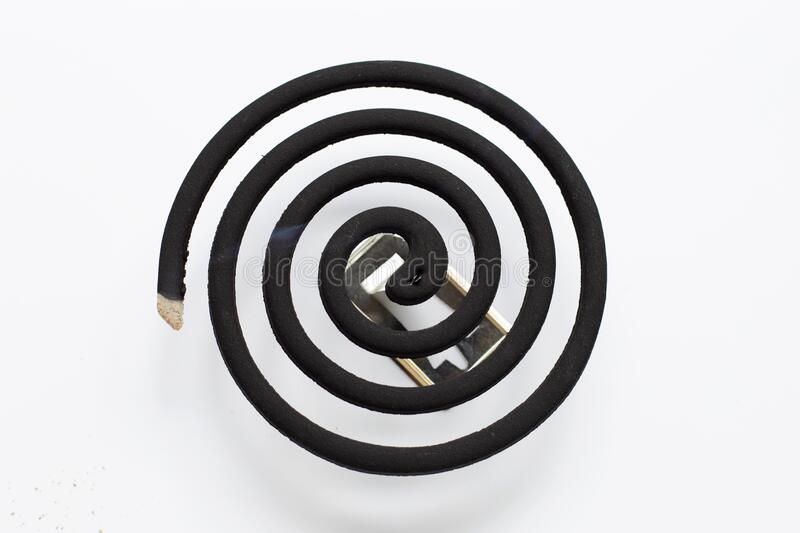 Black spiral mosquito repellent coil on white background. Copy space stock images