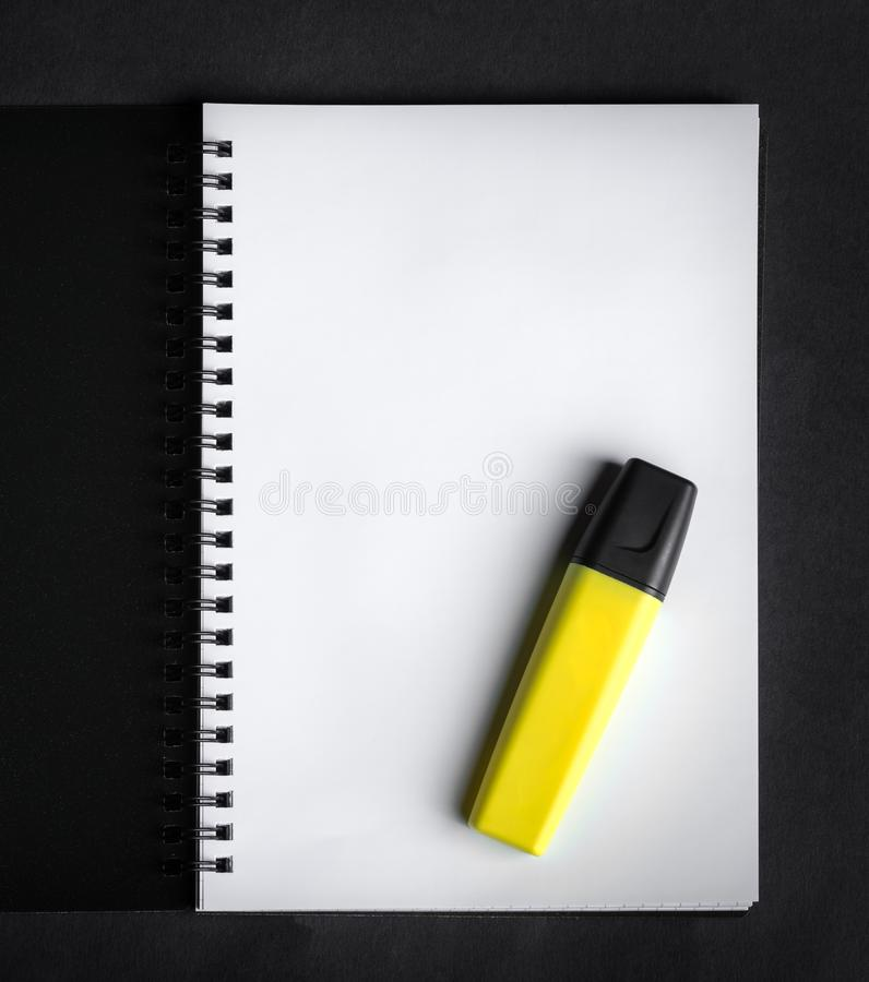 Black spiral notebook with yellow marker stock photo