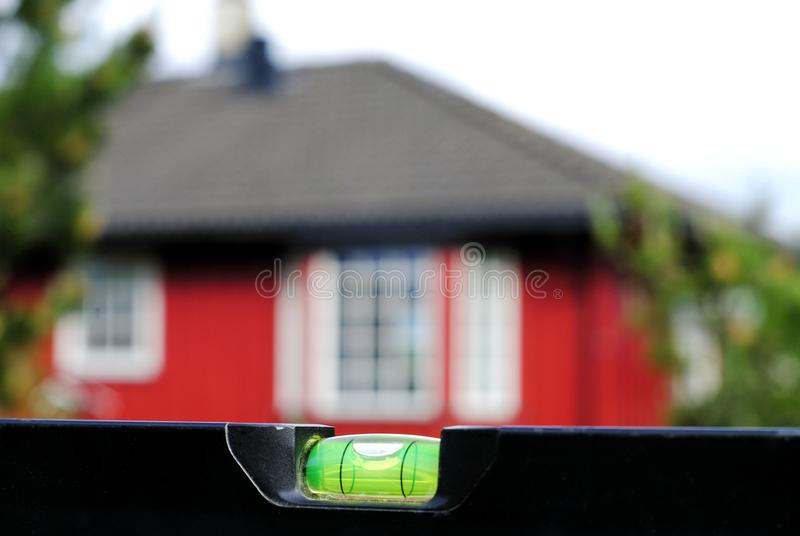Black spirit level on a background of a red house with a black roof royalty free stock photo