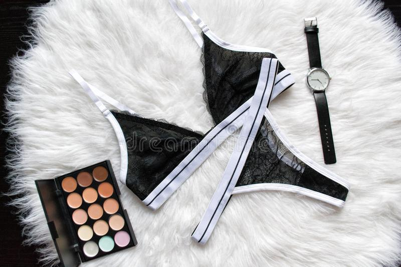Black sports set lace lingerie on a white fur. Watches, eyeshadow. Fashionable concept stock photo