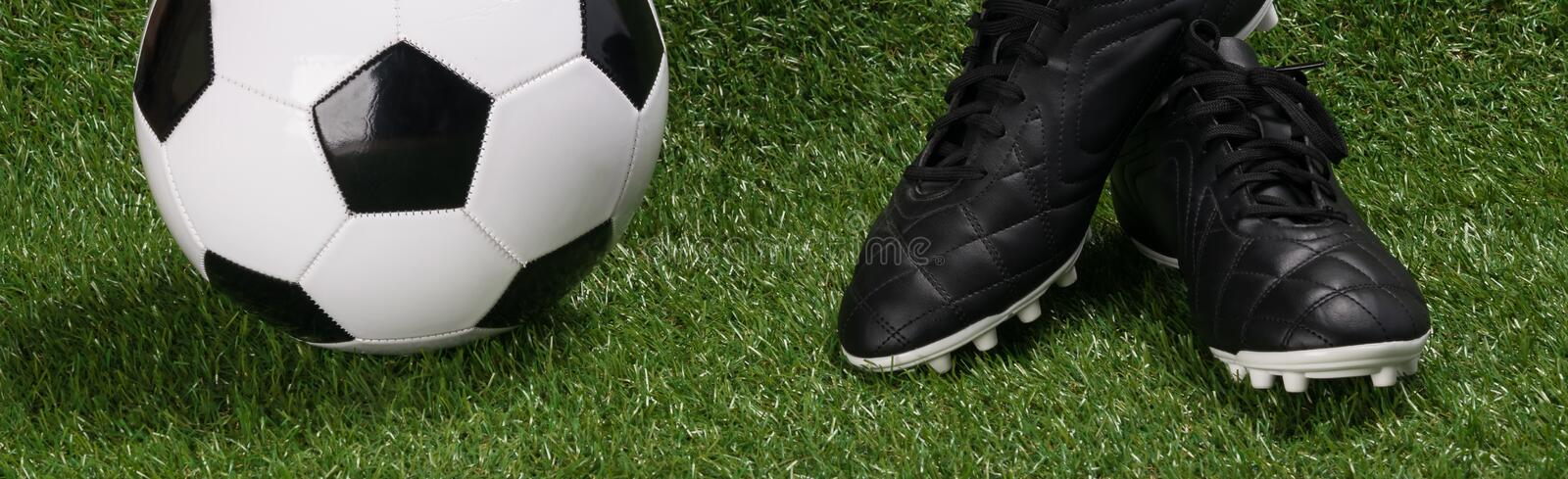 Black sports shoes and a ball for the soccer championship on a long green lawn stock images