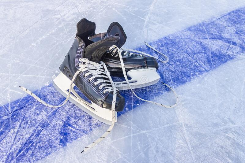 Black sports skates lie on a hockey rink on the blue line royalty free stock image