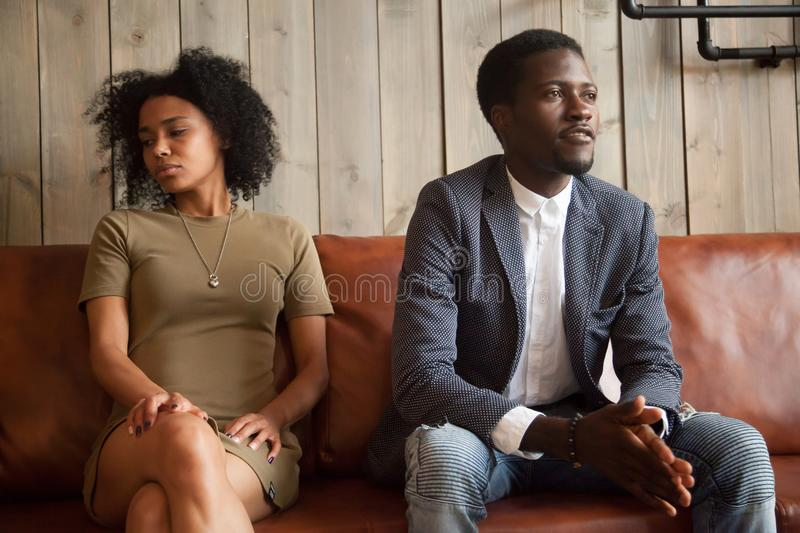 Black spouses sitting on couch aside not ready to compromise. Mad African American husband and wife ignoring each other, not talking, millennial couple in fight royalty free stock images