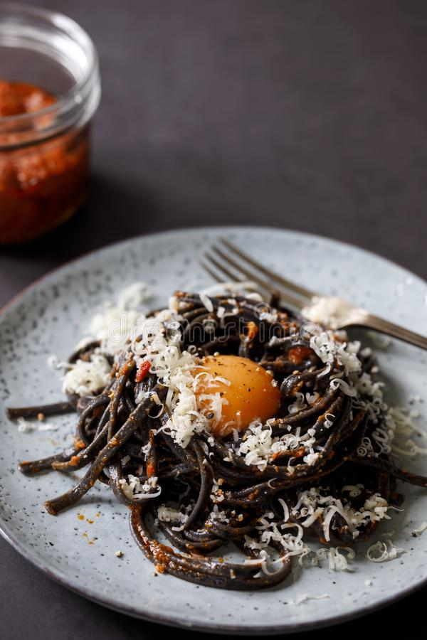 Black pasta with red pesto and egg yolk. Black squid ink pasta with sun dried tomatoes red pesto and egg yolk royalty free stock photos