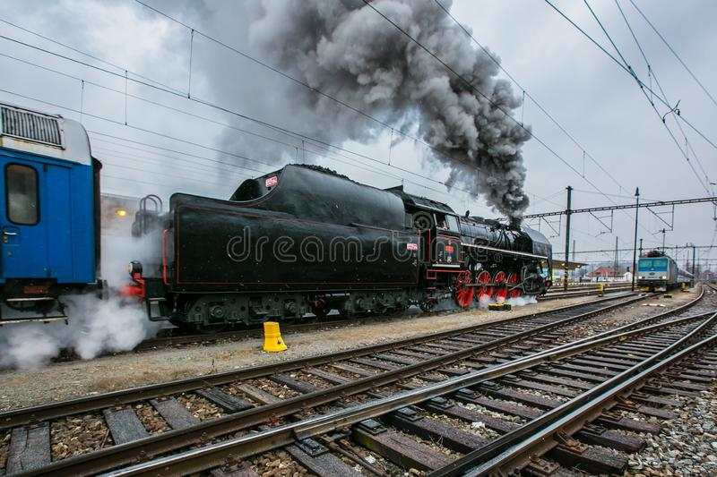 Black steam engine with tender and red wheels belching out steam stock photos