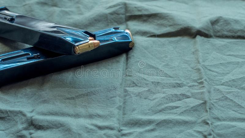 Black steel handgun pistol magazines loaded with hollow point ammunition, resting on an olive drab cloth background.  royalty free stock image