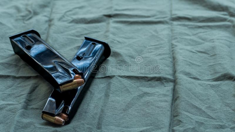 Black steel handgun pistol magazines loaded with hollow point ammunition, resting on an olive drab cloth background stock photos