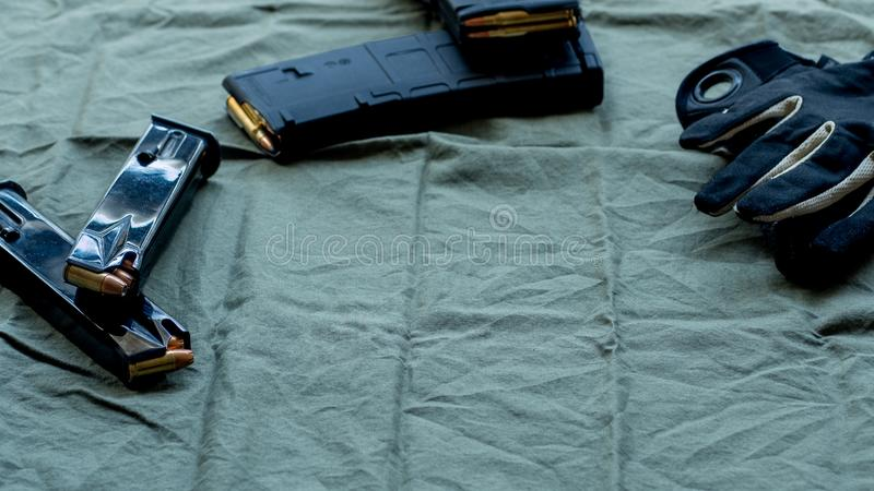 Black steel handgun pistol magazines loaded with hollow point ammunition, soft point loaded polymer AR15/M4 magazines and black an. D tan tactical gloves royalty free stock photos