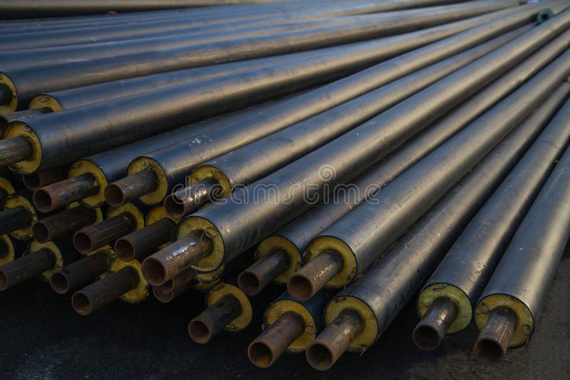 Black steel pipe with heat insulation on the construction site in a plastic tube wrapper lying on the pavement a bunch of horizont. Ally. pipes for supplying gas stock images