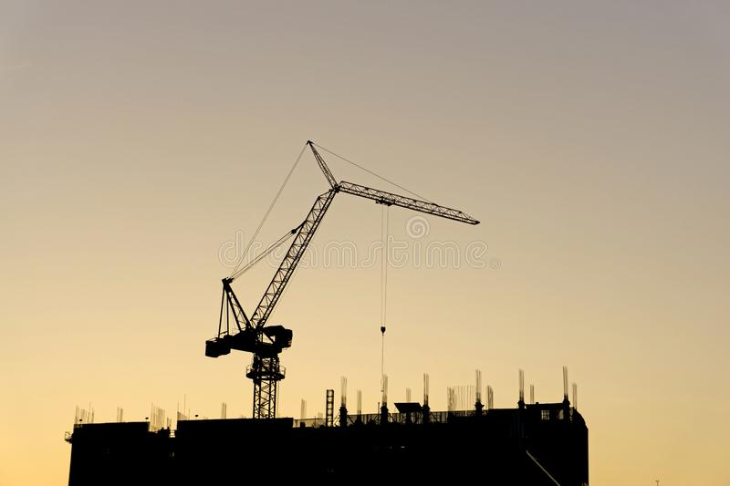 A Black steel tower crane standing on the top of a black building on construction, on evening orange color sky, silhouette royalty free stock photos