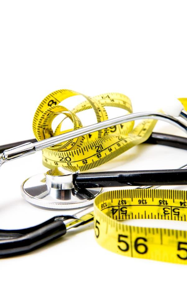 Black stethoscope & yellow diet tape on white stock photos