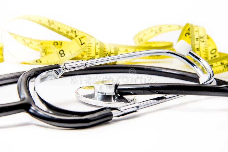 Black stethoscope & yellow diet tape on white stock image