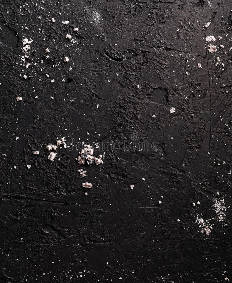 Black stone background with coals and ashes, grey cement texture. Top view, flat lay.  royalty free stock images