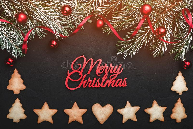 Black stone background, with fir branches adorned with red balls. Biscuits of various shapes. Top view. Effect of lights. Red text merry Christmas stock photography