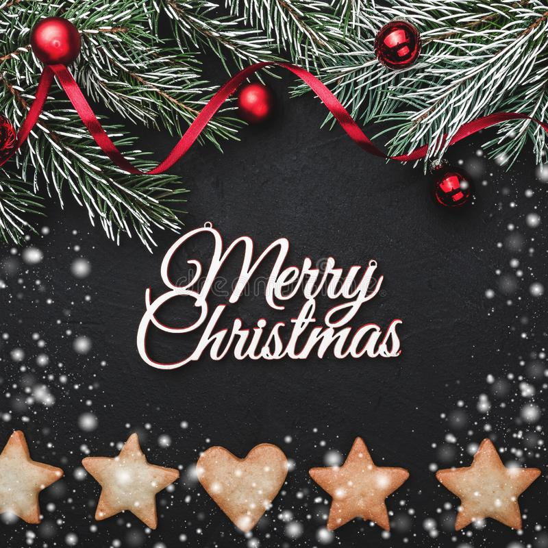 Black stone background, with fir branches adorned with red balls. Biscuits of various shapes. Top view royalty free stock images