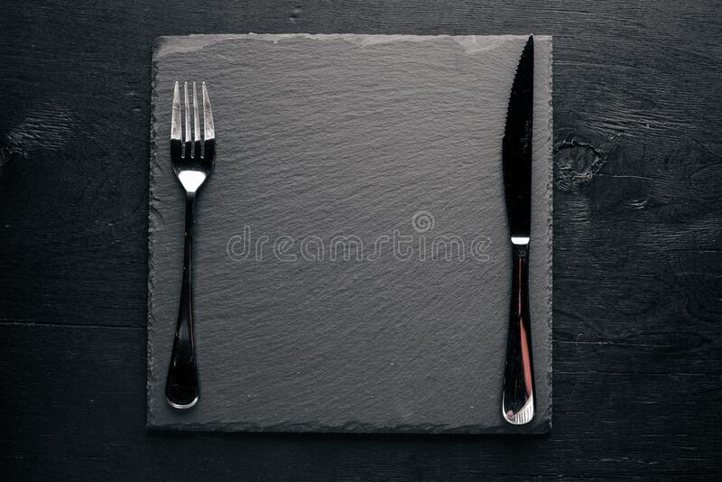 Black stone board with cutlery. On a wooden background. Top review. Free space stock photo